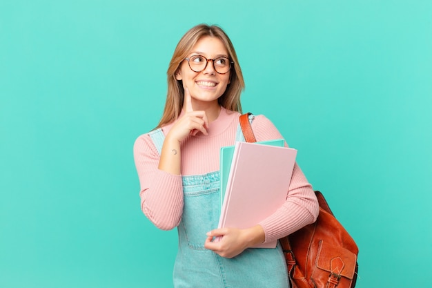 Jonge studentenvrouw die vrolijk lacht en dagdroomt of twijfelt