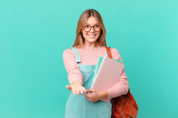 Jonge studentenvrouw die vrolijk lacht met vriendelijk en een concept aanbiedt en toont