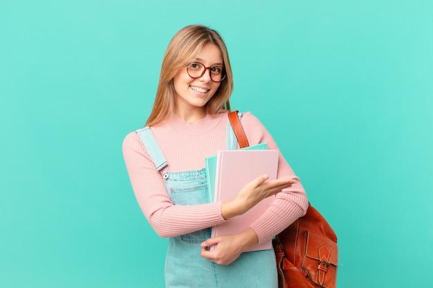 Jonge studentenvrouw die vrolijk lacht, zich gelukkig voelt en een concept toont