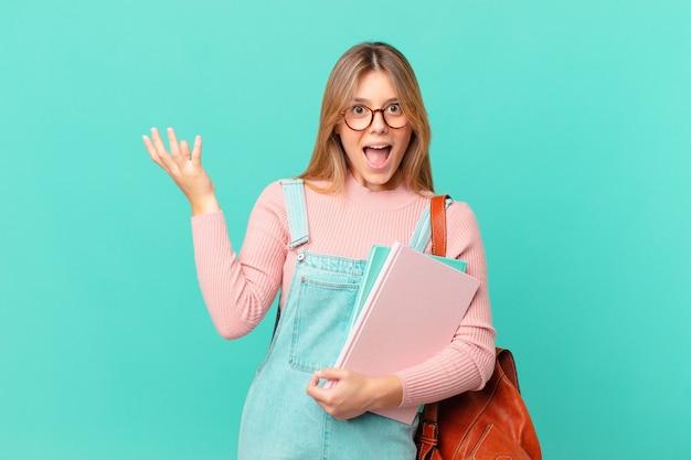 Jonge studentenvrouw die zich gelukkig, verrast voelt en een oplossing of idee realiseert
