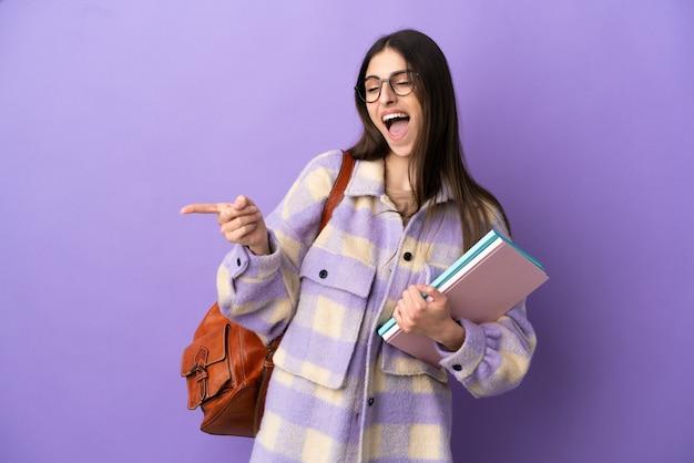 Jonge studentenvrouw geïsoleerd op een paarse achtergrond die met de vinger naar de zijkant wijst en een product presenteert