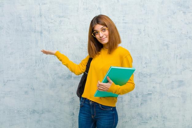 Jonge studentenvrouw glimlachen, die zeker, succesvol en gelukkig voelen, tonend concept of idee op exemplaarruimte aan de kant op grungemuur