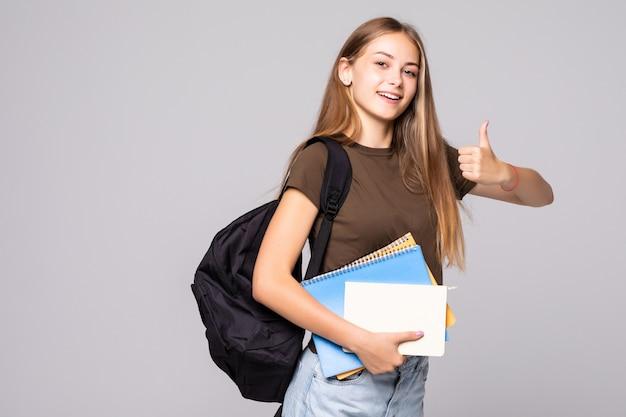 Jonge studentenvrouw met de holdingshand van de rugzakzak met duim omhoog gebaar, dat over witte muur wordt geïsoleerd