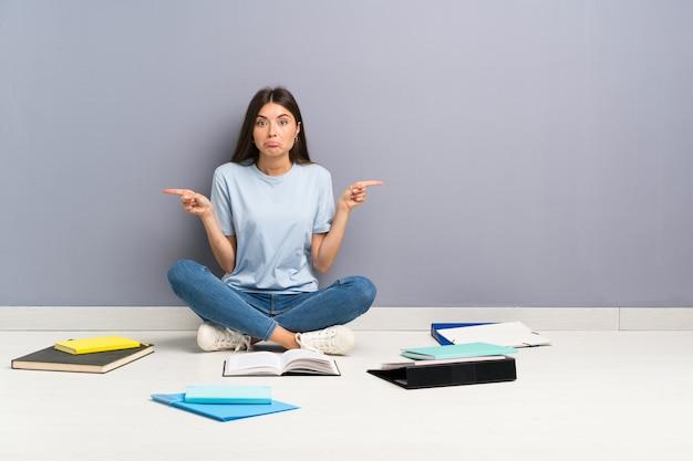 Jonge studentenvrouw met veel boeken op de vloer die naar de zijtakken wijzen die twijfels hebben