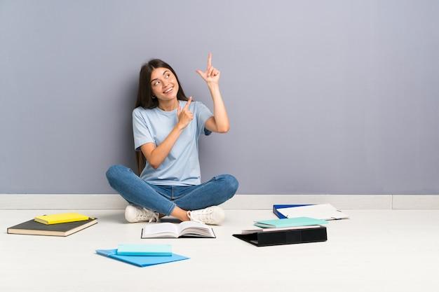 Jonge studentenvrouw met vele boeken op de vloer die met de wijsvinger een groot idee richten