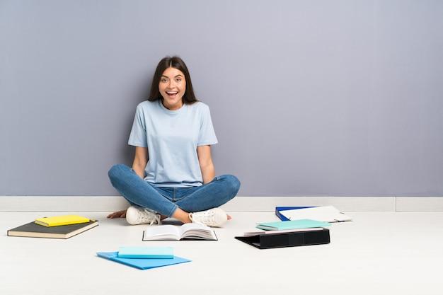 Jonge studentenvrouw met vele boeken op de vloer met verrassingsgelaatsuitdrukking