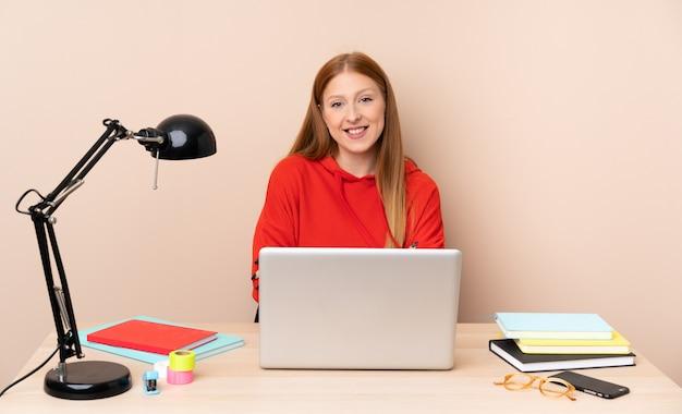Jonge studentenvrouw op een werkplaats met laptop die de wapens in frontale positie houden gekruist