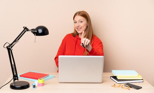 Jonge studentenvrouw op een werkplaats met laptop die en een vinger toont opheft