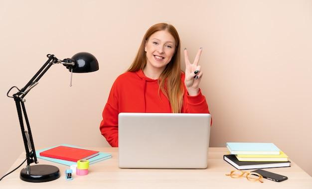 Jonge studentenvrouw op een werkplaats met laptop die en overwinningsteken glimlachen tonen