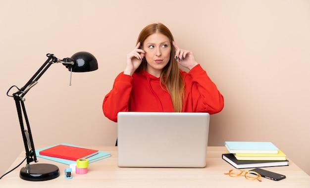 Jonge studentenvrouw op een werkplaats met laptop die twijfels en het denken hebben