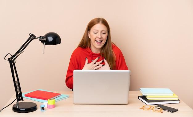 Jonge studentenvrouw op een werkplaats met laptop die veel glimlacht