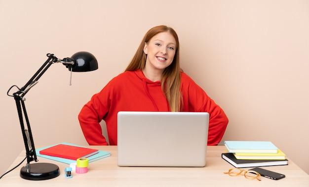 Jonge studentenvrouw op een werkplaats met laptop het stellen met wapens bij heup en het glimlachen