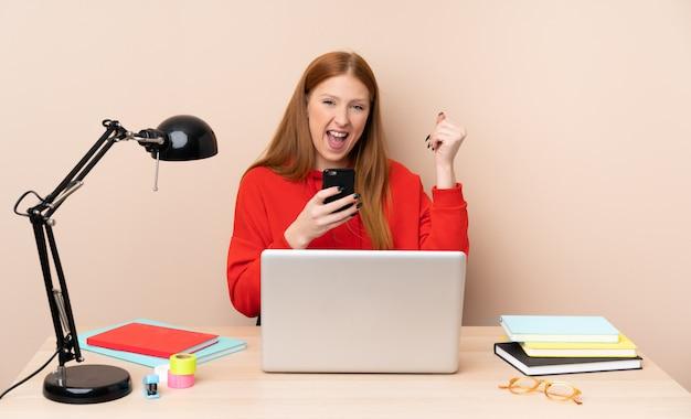 Jonge studentenvrouw op een werkplaats met laptop met telefoon in overwinningspositie