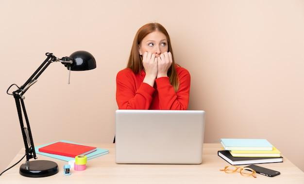 Jonge studentenvrouw op een werkplaats met laptop zenuwachtig en bang die handen aan mond zetten