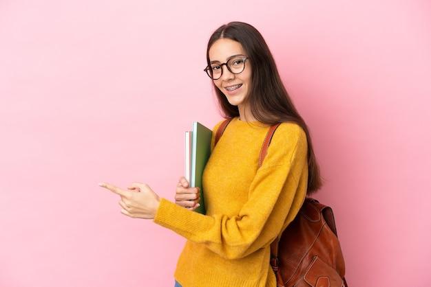 Jonge studentenvrouw over geïsoleerde achtergrond wijzende vinger naar de zijkant