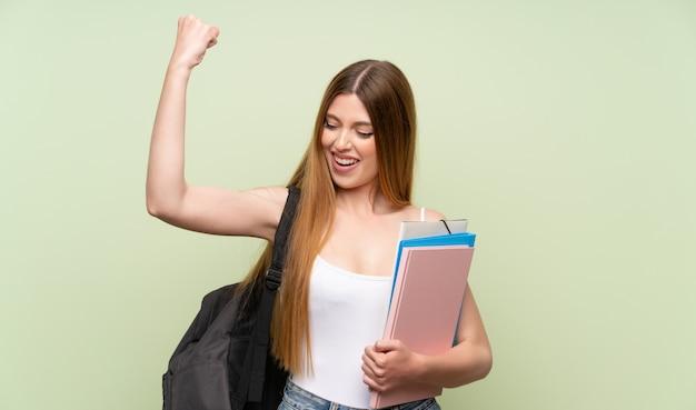Jonge studentenvrouw over geïsoleerde groene achtergrond die een overwinning viert
