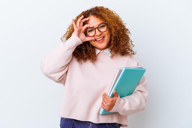 Jonge studentenvrouw over geïsoleerde opgewekte achtergrond die ok gebaar op oog houdt.