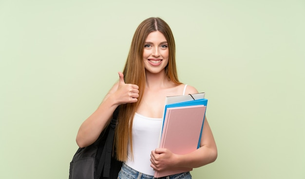 Jonge studentenvrouw over het geïsoleerde groene geven duimen op gebaar