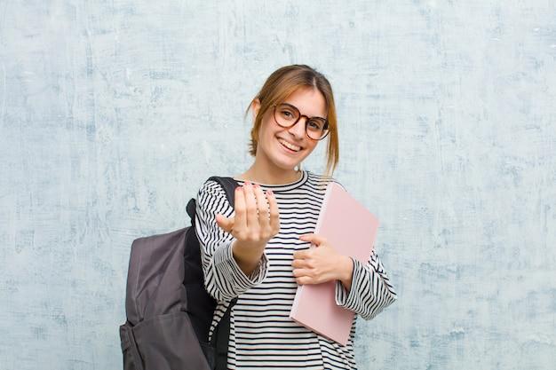 Jonge studentenvrouw voelt zich gelukkig, succesvol en zelfverzekerd, staat voor een uitdaging en zegt: kom maar op! of je te verwelkomen op grunge muur