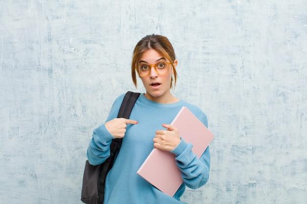 Jonge studentenvrouw voelt zich verward, verbaasd en onzeker, wijst naar zichzelf en vraagt zich af wie, mij? tegen grunge muur achtergrond