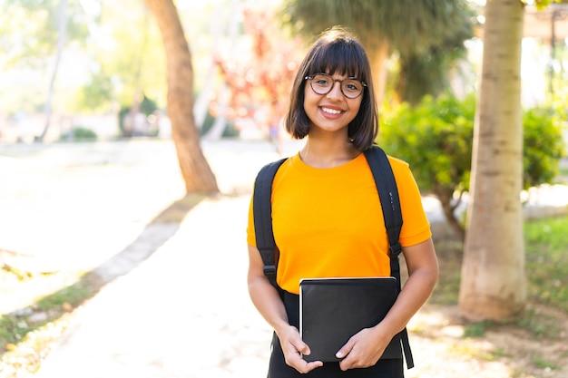 Jonge studentenvrouw wint een park met een notitieboekje met een vrolijke uitdrukking