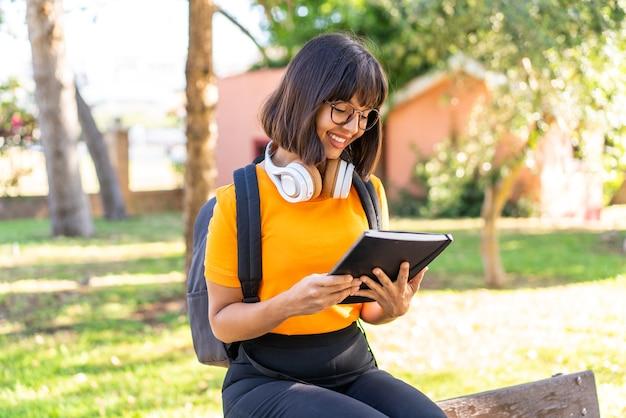 Jonge studentenvrouw wint een park met een notitieboekje