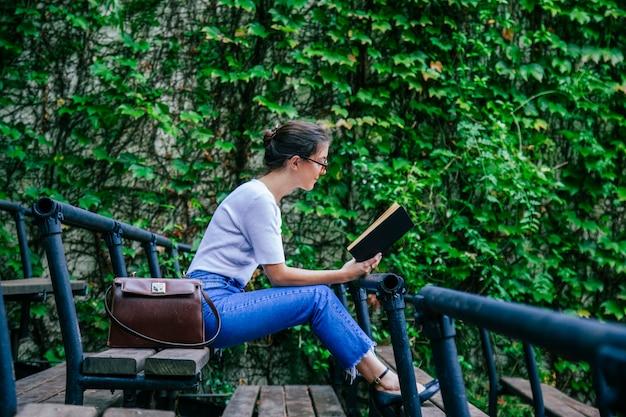 Jonge studentenzitting op de campusbank die met boeken leert