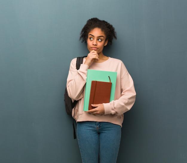 Jonge studentenzwarte die over een idee denkt. ze houdt boeken vast.