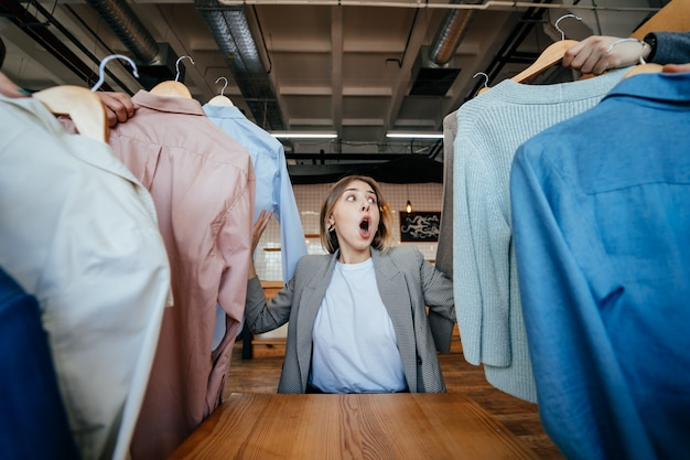 Jonge stylist die door reeks overhemden kijkt voor manier het schieten