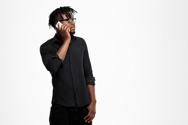 Jonge succesvolle afrikaanse zakenman die op telefoon op wit spreekt.