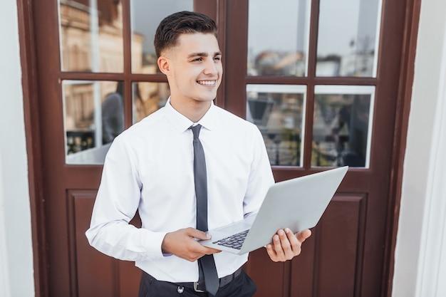 Jonge succesvolle bedrijfsmens in bedrijfsstijl met laptop in zijn handen