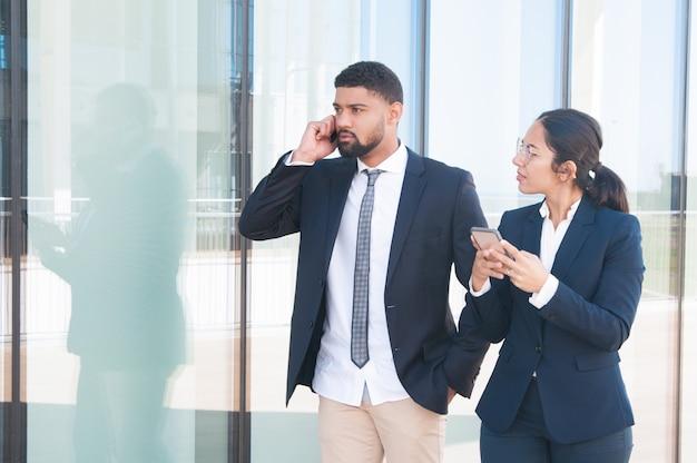 Jonge succesvolle bedrijfsmensen die smartphones gebruiken