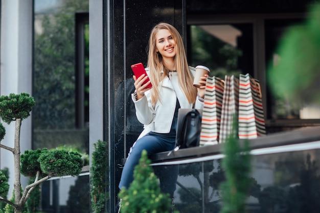 Jonge, succesvolle blonde modieuze vrouw met kopje koffie en telefoon, zit in de buurt van de winkel na haar winkeltijd.