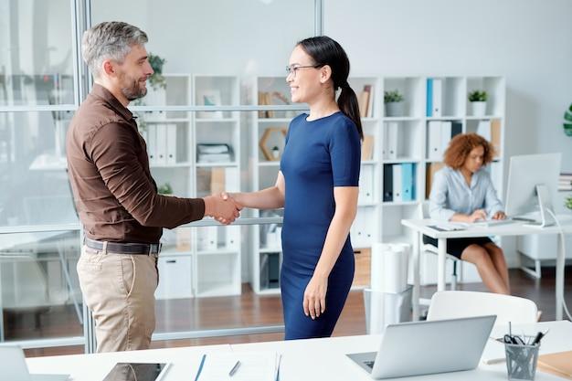 Jonge succesvolle collega's of zakelijke partners in smart casual handen schudden door werkplek na het maken van overeenstemming over werkpunten