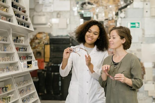 Jonge succesvolle consultant van optiekwinkel toont een van de nieuwe modellen aan de klant terwijl hij haar helpt bij het kiezen van een bril