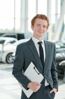 Jonge succesvolle dealer in elegant pak en stropdas met klembord met documenten terwijl hij op nieuwe auto's staat