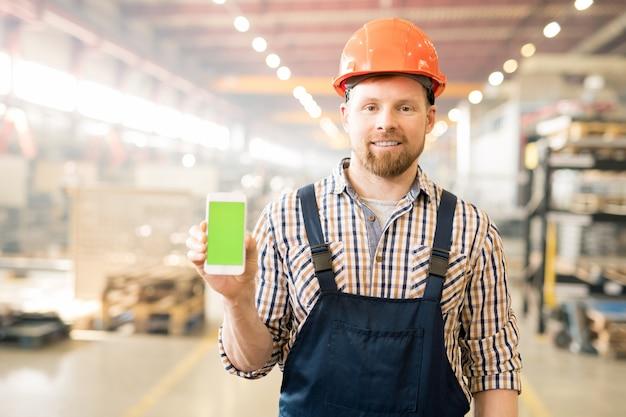 Jonge succesvolle fabrieksingenieur in overall en helm promo tonen op touchscreen van zijn smartphone