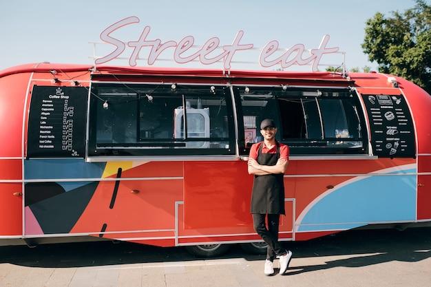 Jonge succesvolle klerk met gekruiste armen die bij de voedselwagen staat