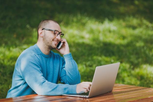 Jonge succesvolle lachende slimme man zakenman of student in casual blauw shirt, bril zittend aan tafel, praten op mobiele telefoon in stadspark met behulp van laptop, buitenshuis werken. mobiel kantoorconcept.