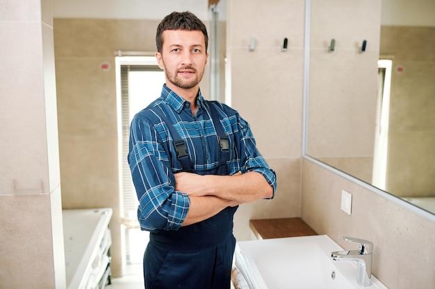 Jonge succesvolle loodgieter in werkkleding staande in de badkamer
