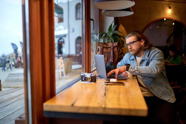 Jonge succesvolle man zit in café en surfen op internet op laptop. freelancer