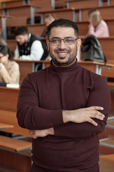 Jonge succesvolle mannelijke leraar die zijn armen kruist bij de borst terwijl hij voor de camera staat tegen studenten die bij een bureau in de collegezaal zitten