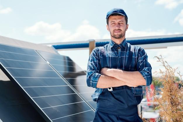 Jonge succesvolle meester van de installatie van zonnepanelen die de armen bij de borst kruist terwijl hij op het dak staat