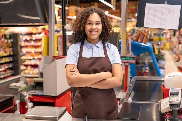 Jonge succesvolle mixed-race verkoopster in werkkleding die haar armen door borst kruist terwijl ze bij de kassa in de supermarkt staat