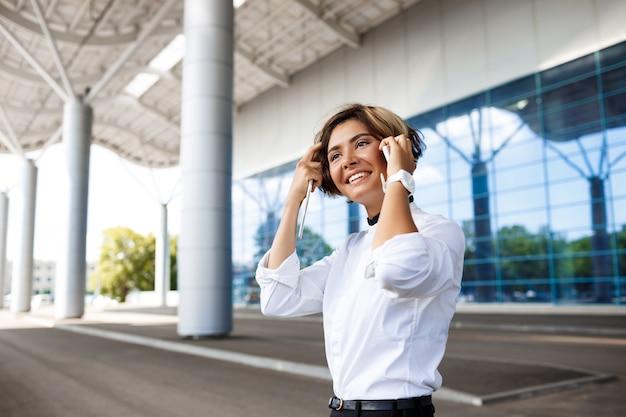 Jonge succesvolle onderneemster die op telefoon spreekt, die zich dichtbij commercieel centrum bevindt.