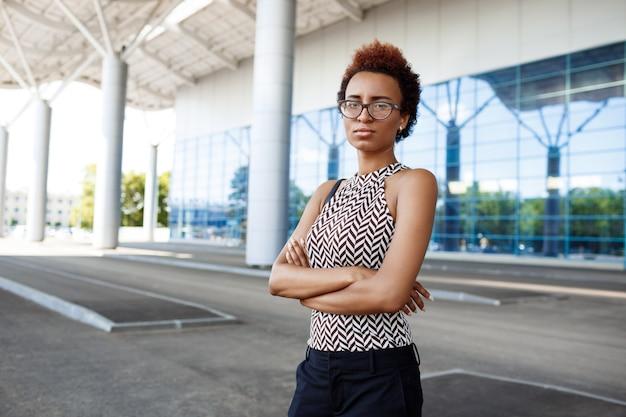 Jonge succesvolle onderneemster in glazen die zich dichtbij commercieel centrum bevinden