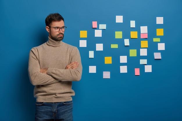 Jonge succesvolle ondernemer staat in een doordachte pose, brainstormt over ideeën voor het ontwikkelen van een startup-project, staat met gekruiste handen tegen blauwe achtergrond, plaknotities geplakt op blauwe muur erachter