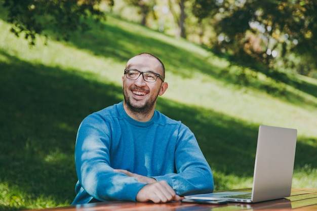 Jonge succesvolle slimme lachende gelukkige man zakenman of student in casual blauw shirt, bril zittend aan tafel met mobiele telefoon in stadspark met behulp van laptop, buitenshuis werken. mobiel kantoorconcept.