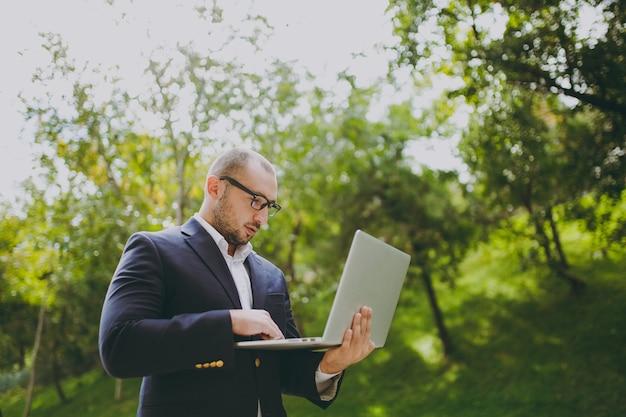 Jonge succesvolle slimme zakenman in wit overhemd, klassiek pak, bril. man permanent en werken op laptop pc-computer in stadspark buiten op natuur achtergrond. mobiel kantoor, bedrijfsconcept.