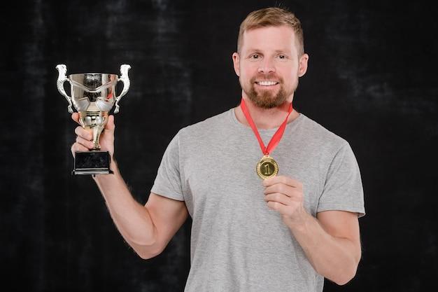 Jonge succesvolle sportman die u zilveren beker en gouden medaille toont terwijl u tegen zwarte achtergrond voor camera staat